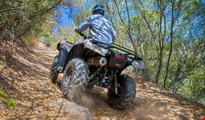 ATV rider viewed from behind riding comfortably up a steep, rugged incline on dusty uneven trail.