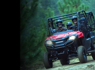 Image of four side-by-side riders driving happily along trail with lush green shrubbery