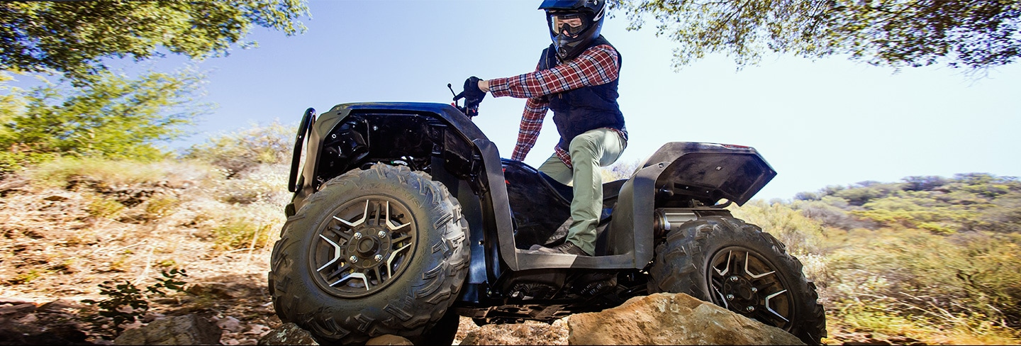 ATV rider in black helmet with red plaid shirt maneuvering over big boulders