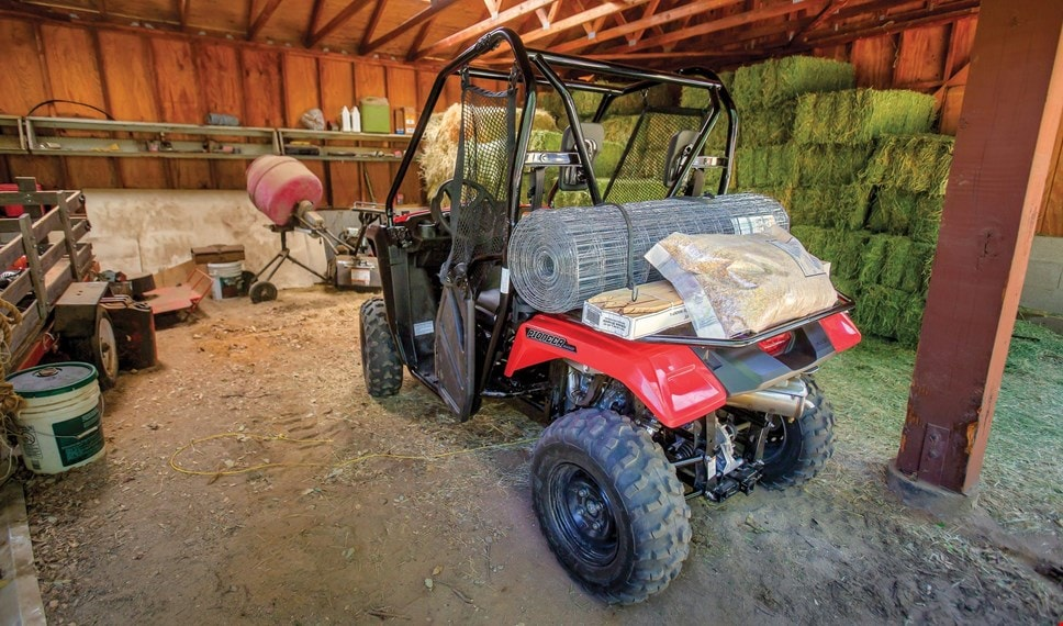 The red Pioneer 500 parked in farm shed loaded with fence materials on rear rack