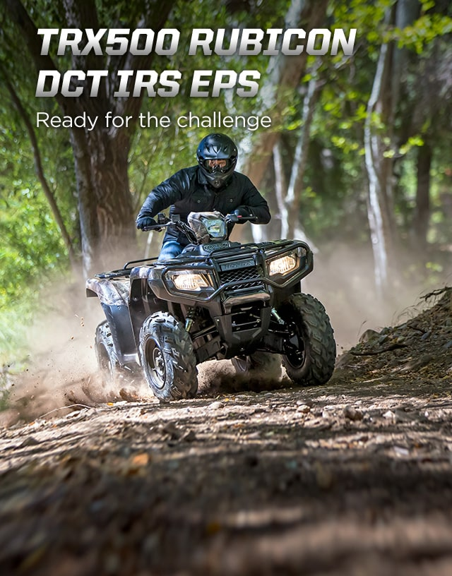 TRX500 Rubicon DCT IRS EPS. Ready for the challenge. Image of ATV rider powerfully steering up rugged dirt trail in the forest