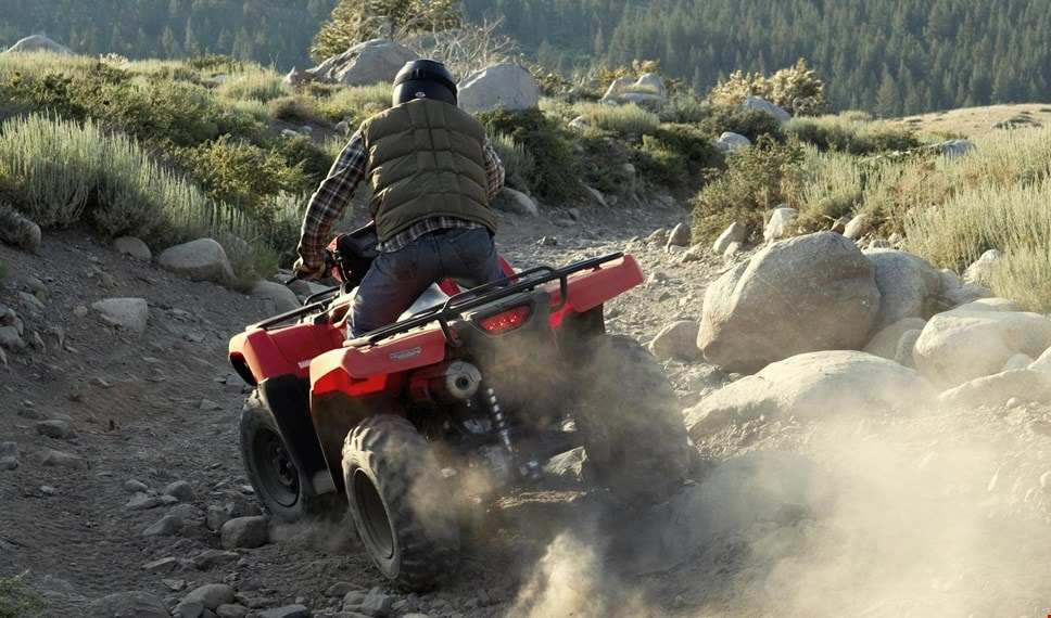 ATV rider viewed from rear, manouevering over large rocks on rugged, sloping trail overlooking forest