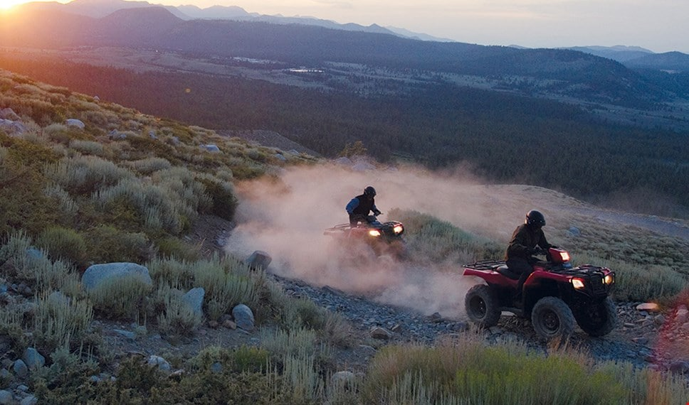 Two ATV riders treading through rocky terrain in the wilderness as the sun begins to set over mountains.