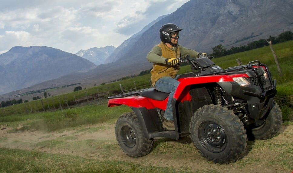 ATV rider leaving a behind a trail of dust while operating the TRX420 over hefty boulders and uneven terrain