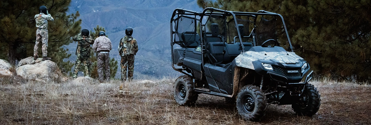 Pioneer 700-4 side-by-side parked in grassy wooded area with four ATV riders dressed in black helmets and camoflauge looking out over a hilly ridge in the background