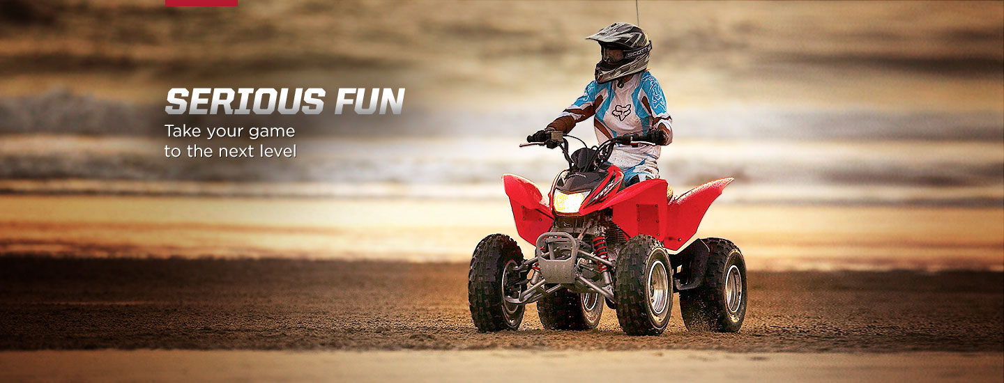 Serious Fun. Take your game to the next level. Image of determined rider in ATV sport suit riding red ATV on rocky incline.