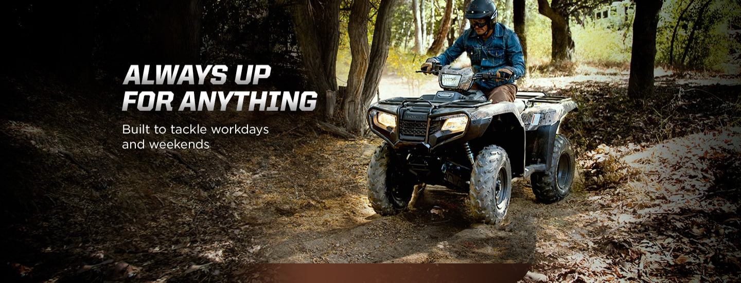 Always up for anything. Built to tackle workdays and weekends. Image of man in denim shirt riding black ATV on muddy forest trail.
