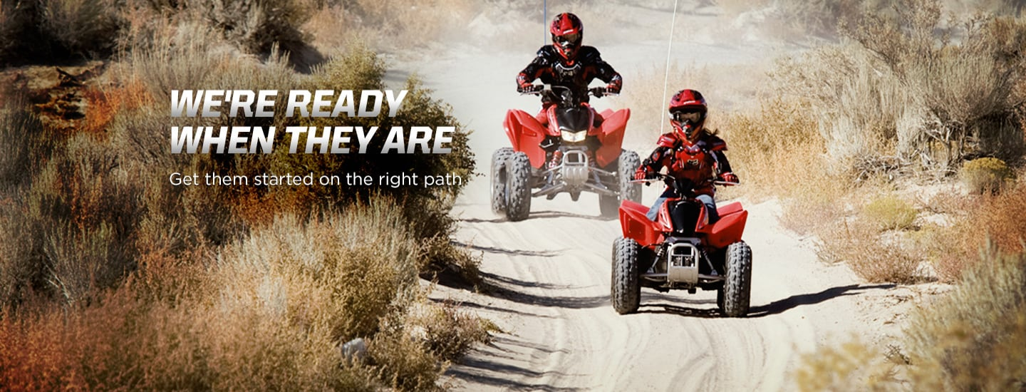 We're ready when they are. Get them started on the right path. Image of young child riding red ATV down dusty trail with adult riding behind in matching ATV