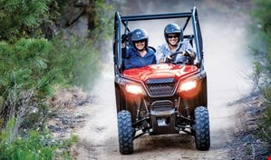 Smiling couple high on adrenaline while accelerating down a narrow dirt trail in red Pioneer 500