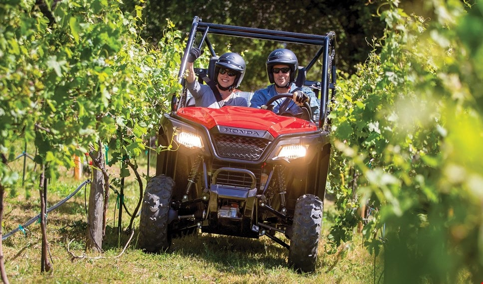 Couple in red Pioneer 500 driving happily through narrow vineyard row