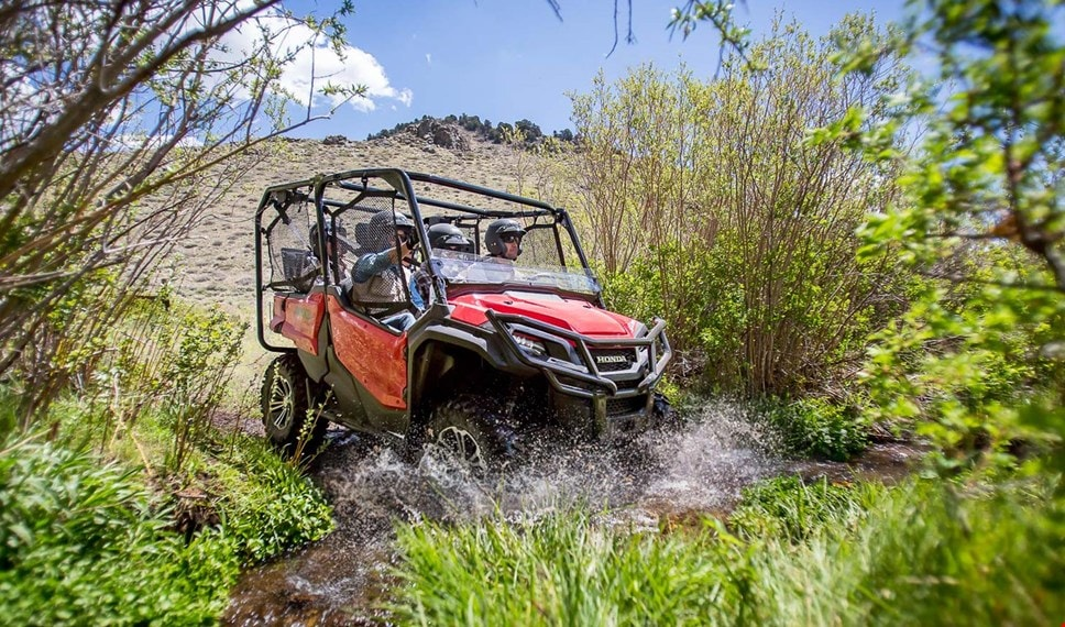 Four riders having fun whizzing down rocky trail in red Pioneer 1000-5 EPS equipped with hard roof and durable steel front bumper