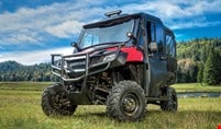 The red Pioneer 700-4 dressed up with durable hard front doors, glass windshield and mounted light bar and auxilary lights, parked in scenic forest meadow