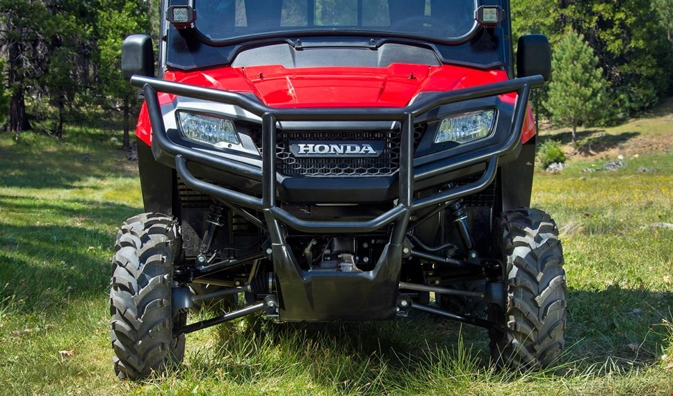 The red Pioneer 700-4 with strong steel front bumper and mounted side mirrors and auxilary lights