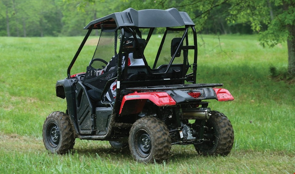 The red Pioneer 500 with durable hard roof driving through green grassy field