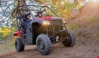 Image of happy couple in red Pioneer 500 exploring the sunny outdoors on rugged trail