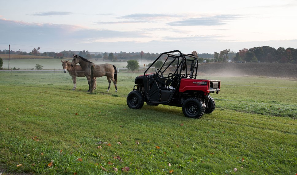 Side view of Pioneer 520 in front of horses