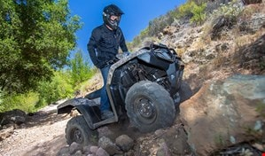 ATV rider in standing position scaling over big boulders on steep rugged slope.