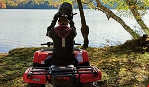 Man taking helmet off in front of pond on ATV