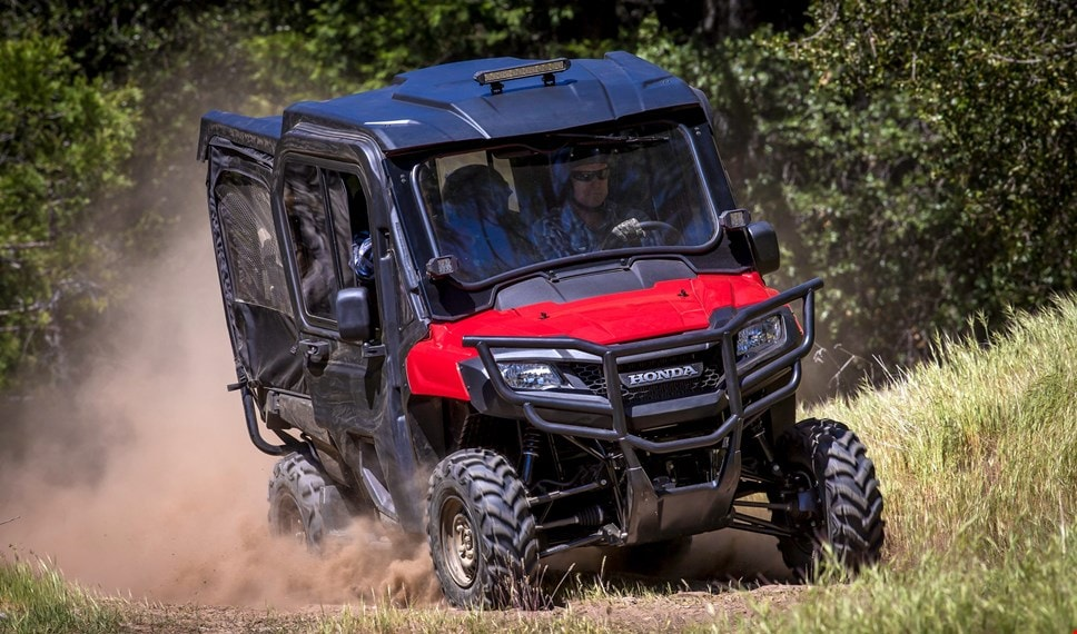 The red Pioneer 700-4 equipped with hard roof, glass windshield and fabric front doors cruising effortlessly over rugged dusty terrain