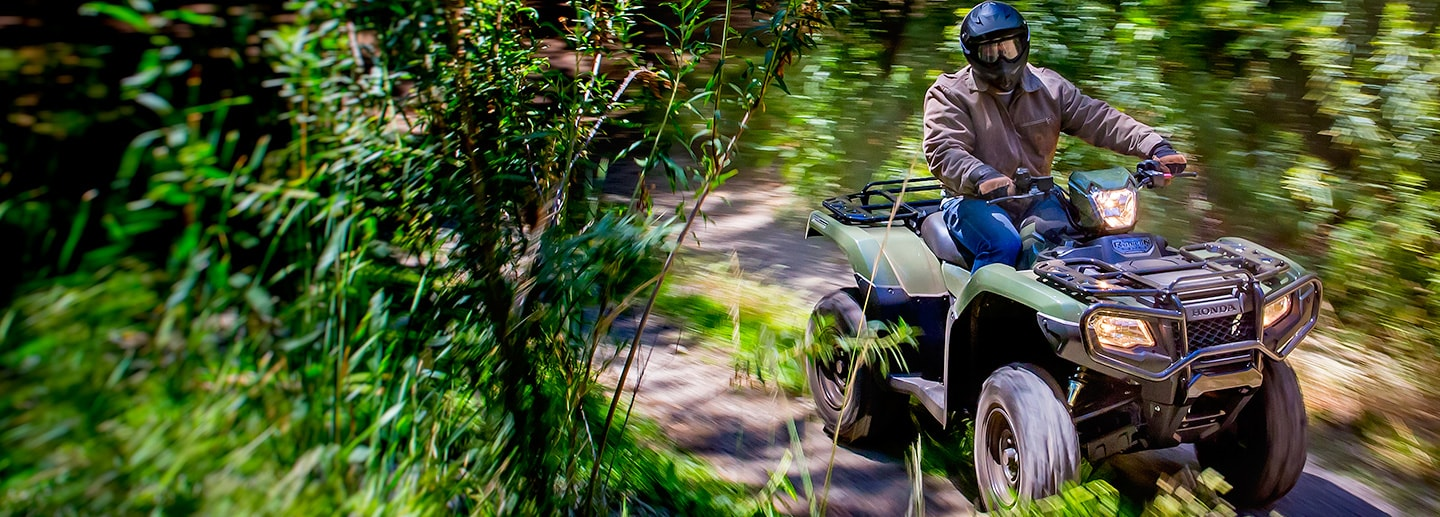 ATV rider on trail accelerating through lush green shrubbery