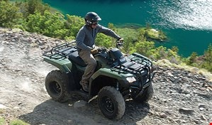 Rider driving TRX420 Rancher in colour Olive on rugged trail along turquoise lake