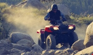Rider on TRX420 Rancher manouevering over large rocks on a rugged trail incline.